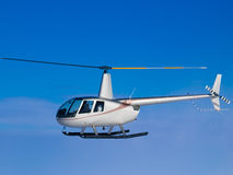 Helicopter flying in blue sky side Stock Photos