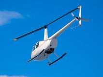 Helicopter flying in blue sky view from under and behind Stock Photography