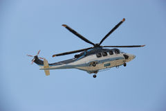 Helicopter. Is flying in bright blue sky Stock Image
