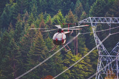 Helicopter Flying Next To Power Lines. This helicopter is flying dangerously close the power lines Royalty Free Stock Photography