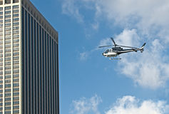 Helicopter flying next to skyscraper royalty free stock photos