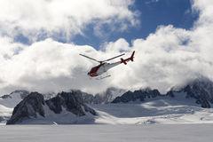 Helicopter flying over glacier stock photos