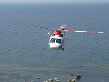 Helicopter flying over sea Royalty Free Stock Photo