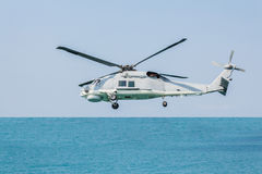Helicopter flying over the sea Stock Photos