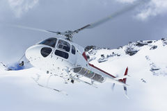 Helicopter Flying Over Snowy Mountain Peaks Stock Photo