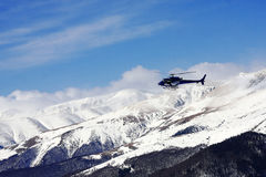 Helicopter flying over the snowy mountains Stock Photos