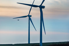 Helicopter flying past wind turbines Stock Photos