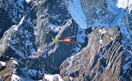 Helicopter is flying between snow mountains peak in high Himalay Stock Photos
