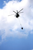 Helicopter Flying Water. Helicopter with loaded water basket on it's way to douse a fire Royalty Free Stock Photos