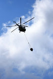 Helicopter Flying Water. Helicopter with loaded water basket on it's way to douse a fire Stock Photography