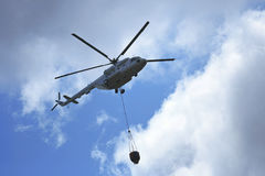 Helicopter Flying Water. Helicopter with loaded water basket on it's way to douse a fire Royalty Free Stock Photography