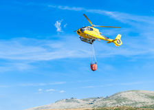 Helicopter,forest fire,water,rescue,uncontrolled fire,extinguish,firefighters,fire,civil protection,forestry,forest ranger,militar. Helicopter on river bed with Royalty Free Stock Photo