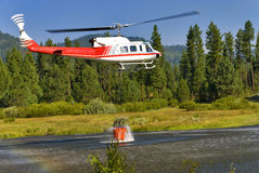 Helicopter full of water ready to fight a fire Stock Image