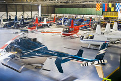 Helicopter Hangar, Full of Robinson R44. Helicopter charter business, hangar full of Robinson R44, and Bell 407's in the back row Stock Photography