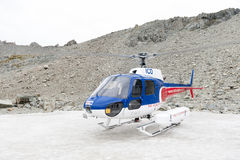 Helicopter from The Helicopter Line Company landing on snowcapped mountain peak around Aoraki Mount Cook and Mount Cook National P Stock Photo