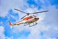 Helicopter. White-red flying in the sky stock photography