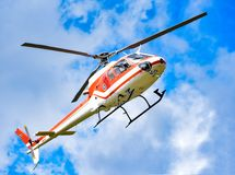 Helicopter. White-red flying in the sky royalty free stock images