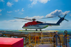 A helicopter landed on offshore drilling rig. With blue sky in background stock image