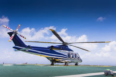 Helicopter landed at top of deck at offshore oil and gas platform. Royalty Free Stock Image