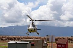 Helicopter Landing. In Hawaii landing pad, blue mountains in background and clouds in sky Stock Image