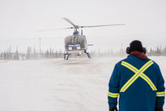 Helicopter Landing at Airport in Snowy Location. With Ground Marshall in Foreground Wearing Safety Jacket Royalty Free Stock Image