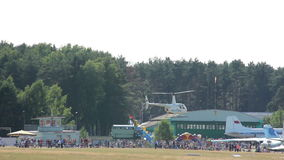 Helicopter landing, airshow, crowded. Helicopter takes off, goes down, extreme games in the helicopter near the forest, a helicopter airport, rescue operation stock footage