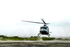 Helicopter landing. A helicopter makes its landing on a dusty fieldrn Stock Image