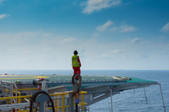 Helicopter landing officer on helicopter deck. Helicopter landing officer (HLO) on helicopter deck of offshore oil rig royalty free stock photo