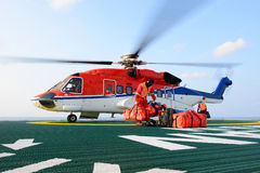 The helicopter landing officer loading baggage to helicopter at Stock Photography