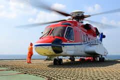 The helicopter landing officer take care loading baggage to heli Royalty Free Stock Photos