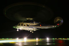 Helicopter landing in offshore oil and gas platform on deck or parking area. Helicopter night flight training of pilot Royalty Free Stock Photo