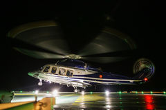 Helicopter landing in offshore oil and gas platform on deck or parking area. Helicopter night flight training of pilot Royalty Free Stock Photography