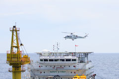Helicopter landing on offshore oil rig, Passenger transfer to offshore oil and gas platform for work. Stock Photo