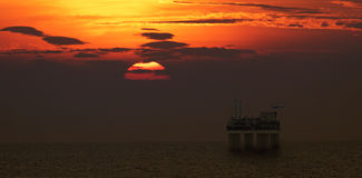 Helicopter landing on oil platform with beautiful sunset scene Stock Photos