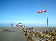 Helicopter Landing Pad. A helicopter stationed at a landing pad with a windsock indicating strong wind stock photo