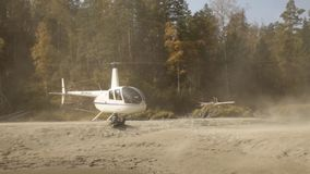 Helicopter landing on a riverbank in a mountainous area. low-flying helicopter in the highlands. Small lightweight