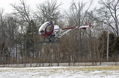 Helicopter landing in a small field with snow Royalty Free Stock Photo