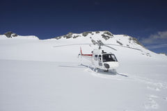 Helicopter Landing On Snowy Mountain Top Royalty Free Stock Image