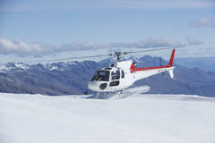 Helicopter Landing On Snowy Mountain Top Stock Photo