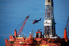 Helicopter Leaving A Semi Submergible Rig. Stock Photos