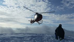 The helicopter left skiers on the slope of the mountain and flew raising a cloud of snow stock video footage