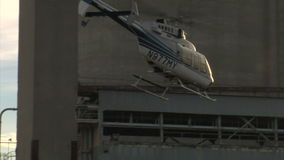 Helicopter lifts off and flies between buildings stock footage