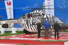Helicopter at MAKS-2013. Three men stand by a helicopter with animal print at International Aerospace Salon MAKS-2013. Taken on August 30, 2013 in Zhukovsky Stock Image