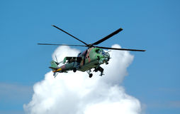 Helicopter Mi-24. Opposite white cloud royalty free stock photo