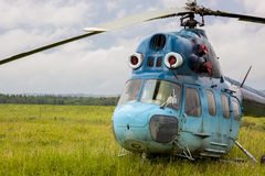 Helicopter MI-2. Blue helicopter MI-2 in green grass on the aerodrome Stock Photos