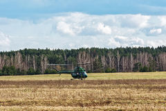 The helicopter MI-2 landed on the field near the forest belt Stock Photography