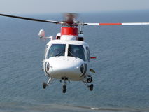 Helicopter in midair over sea Royalty Free Stock Photo