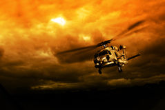 Helicopter in mission. War helicopter in flight against a dramatic red sky Royalty Free Stock Images