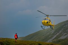 Helicopter in mountain rescue. HEALTH SUPPORT IN HIGH MOUNTAIN WITH HELICOPTER Royalty Free Stock Images