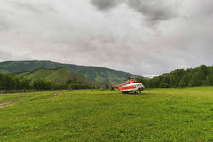 Helicopter in the mountains. On the field in the summer in a thunderstorm Stock Photos